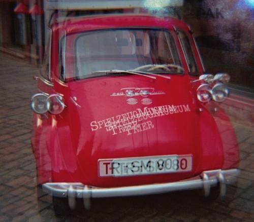 Das Bild ist eine verwackelte/mehrfachbelichtete Aufnahme von einem roten GoGo, einem Werbefahrzeug vom Spielzeugmuseum Trier