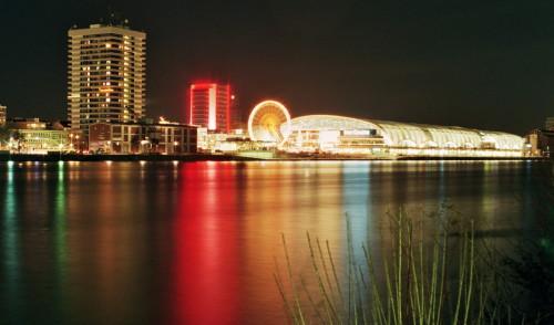 Die Nachtaufnahme zeigt ein Einkaufszentrum (die Rheingalerie), davor ein Riesenrad und beleuchtete Hochhäuser. Es spiegelt sich alles im Rhein.