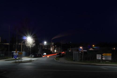 Das Bild zeigt eine Straße in Schöningen, man sieht die Rücklichter eines Autos als Streifen, im Hintergrund der Schornstein vom Kraftwerk Buschhaus