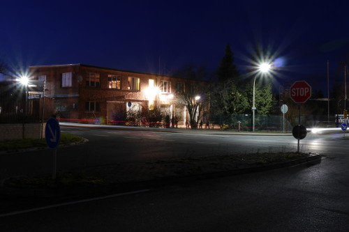 Das Bild zeigt die THW-Unterkunft in Schöningen bei Nacht. Ein flaher Gewerbebau. Im Vordergrund sind Straßen und Straßenschilder