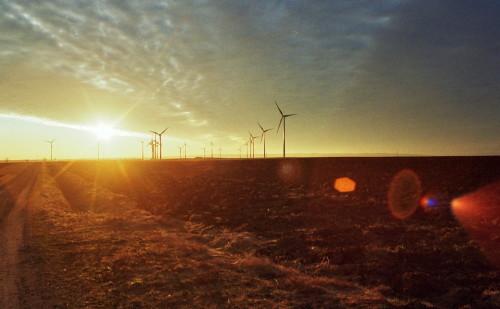 Das Bild zeigt einen Sonnenuntergang, die Sonne steht an der Wolkendecke. Man sieht Windräder, einen Feldweg und die Sonne hat Lensflares hinterlassen