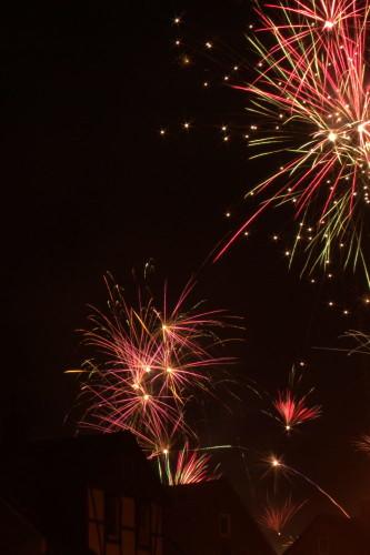 Das Bild zeigt Feuerwerksraketen über Häusern.