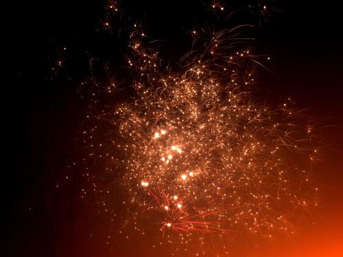 Das Bild zeigt viele glühende Punkte (wie Sterne) eines Feuerwerks. Teile des Bildes sind durch roten Nebel gefärbt.