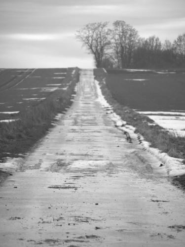 Das s/w-Foto zeigt einen Feldweg, der einen Berg hinausfeht. Man sieht auf dem Berggipfel Bäume und auf dem Weg die Reste von Schnee und Eis.