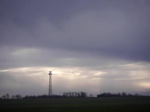 Das Foto zeigt einen Mobilfunkmasten, im Hintergrund sehr dicke Wolken