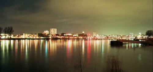 Das Bild zeigt eine Nachtaufnahme der Stadt Ludwigshafen, im Vordergrund ist der Rhein zu sehen, in ihm spiegeln sich die LIchter der Stadt
