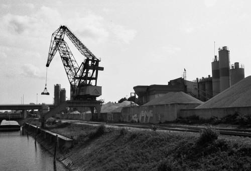 Das s/w-Foto zeigt ein Kieswerk mit Silos, davor ein großer Kran und ein Schiffskanal