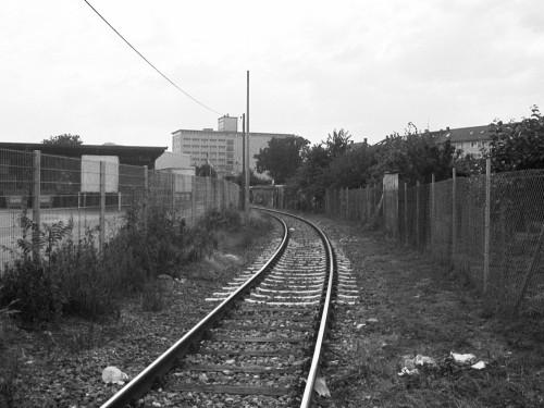 Das s/w-Foto zeigt ein Eisenbahngleis in einem Industriegebiet, rechts und links sind Zäune