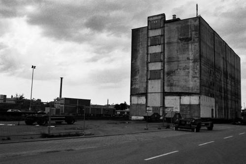 Das Foto zeigt ein altes Industriegebäude, davor Container und leere LKW-Anhänger