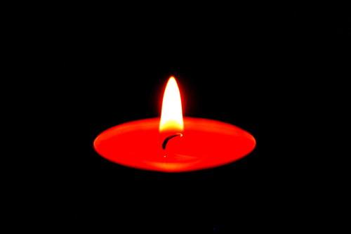Das Bild zeigt ein brennendes, rotes Teelicht in der Dunkelheit