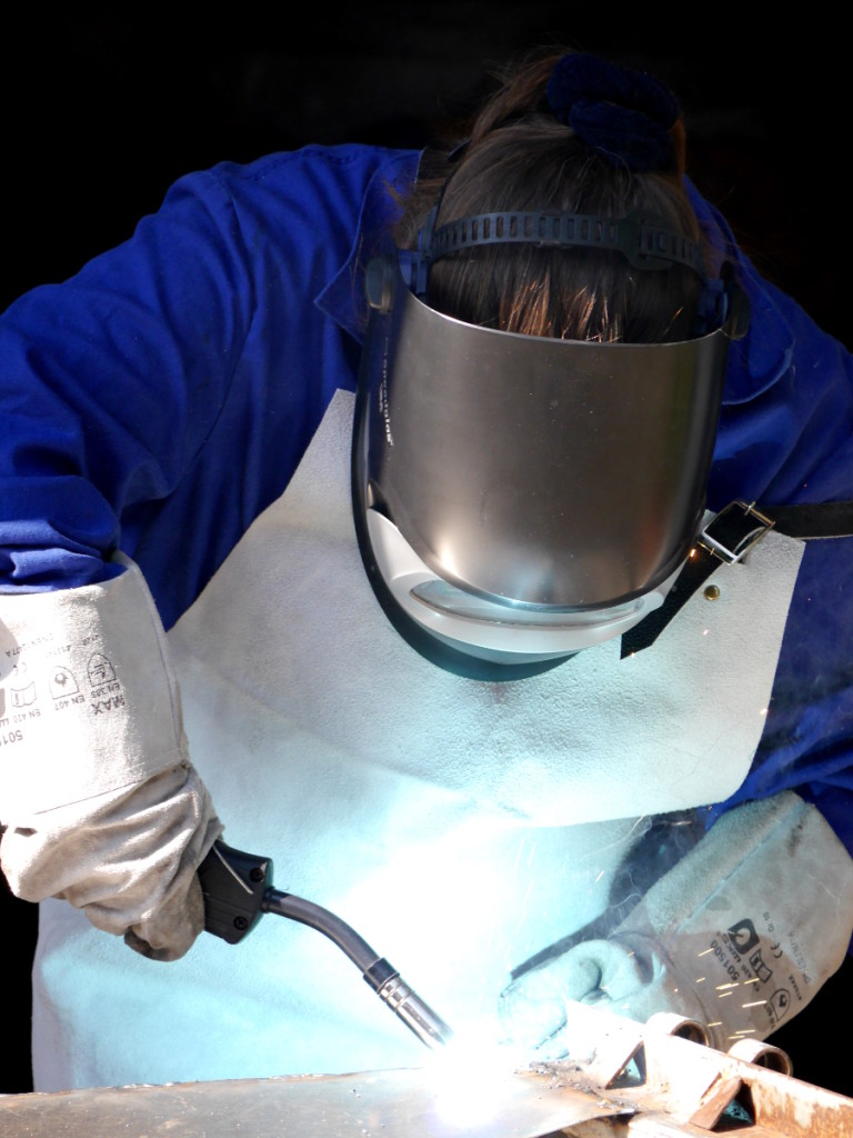Das Foto zeigt eine Frau beim Schutzgas-Schweißen. Sie trägt blaue Arbeitskleidung, eine Lederschürze, Lederhandschuhe und einen schwarzen Schweißhelm