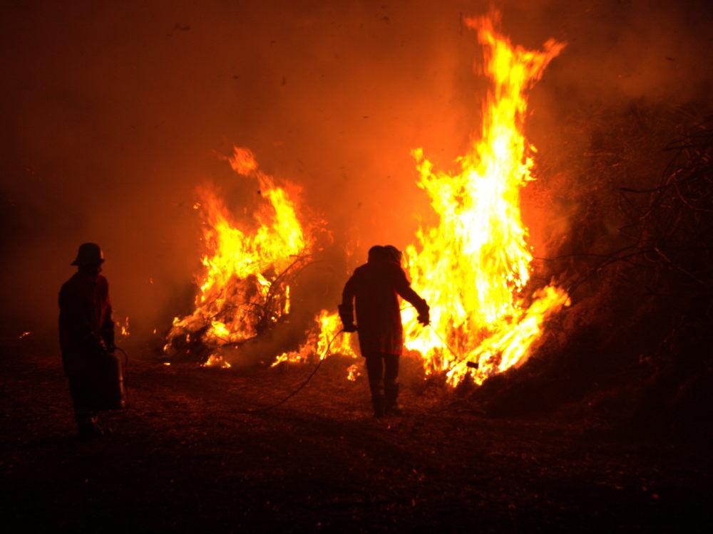 Das Foto ist beim anzünden des Osterfeuers entstanden, die Feuerwehrleute zünden das Stroh mit einem Gasbrenner an
