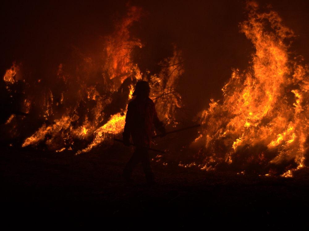 Ein Feuerwehrmann geht mit zwei Mistforken vor dem Osterfeuer