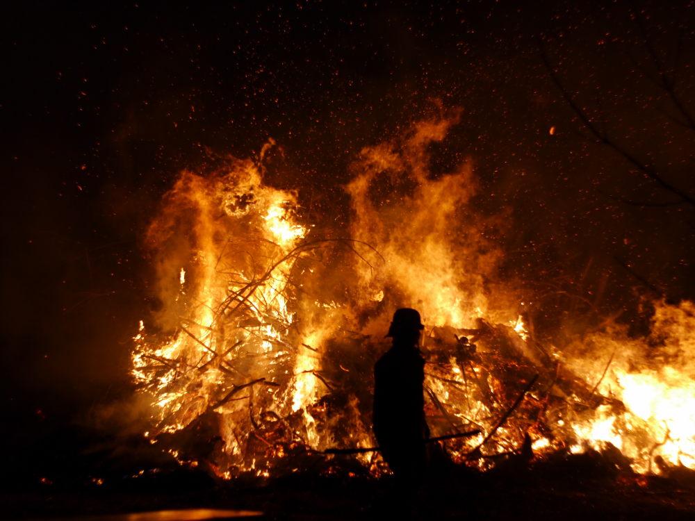 Ein Feuerwehrmann vor dem brennenden Osterfeuer