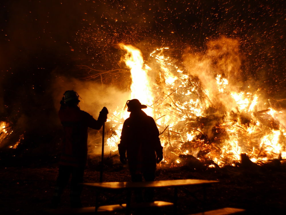 Zwei Feuerwehrmänner betrachten das Osterfeuer.