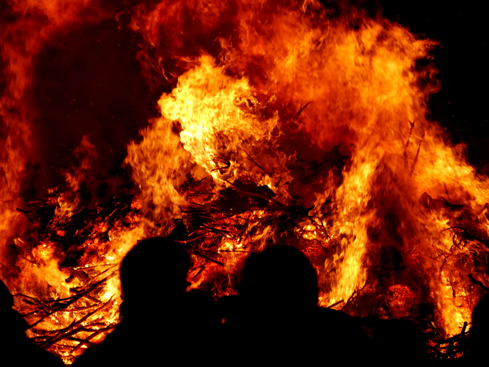 Das Foto zeigt das brennende Osterfeuer, davor sieht man als Silouette die Köpfe der Besucher