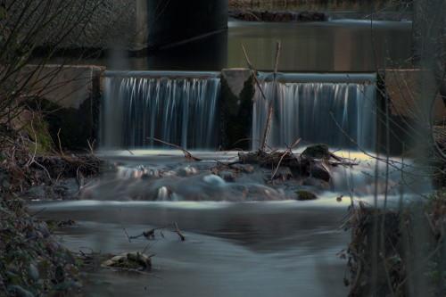 Das Foto zeigt ein Wehr in einem Bach, das Wasser strömt über das Wehr, dann ein wenig über Felsen. Im Fluss liegen Äste und ähnliches. Durch die Lange Belichtungszeit sind die Wassertropfen Silberfäden