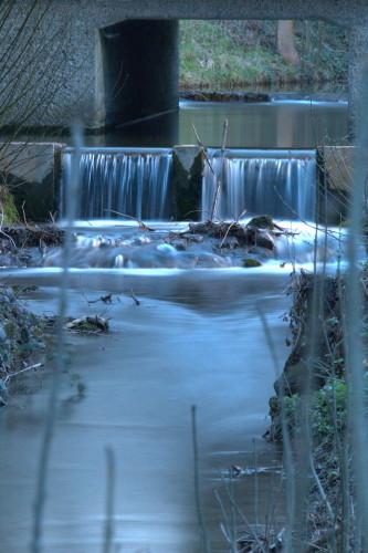 Das Foto zeigt ein Wehr in einem Bach, das Wasser strömt über das Wehr, dann ein wenig über Felsen. Im Fluss liegen Äste und ähnliches. Durch die Lange Belichtungszeit sind die Wassertropfen Silberfäden. Das BIld ist im Hochformat, man sieht viel Bach, wenig Rand.