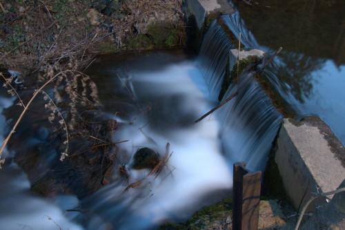 Das Foto zeigt ein Wehr in einem Bach, das Wasser strömt über das Wehr, dann ein wenig über Felsen. Im Fluss liegen Äste und ähnliches. Durch die Lange Belichtungszeit sind die Wassertropfen Silberfäden.