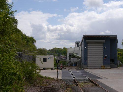 Das Foto zeigt den Gleisanschluß der Schachtanlage Asse, Mittig ist das Tor im Gleis, daneben eine Halle. Man sieht, wie die Gleise zum Schacht verlaufen. Durch die andere Perspektive sieht man die oberen Räder des Förderturms über der weissen Schachthalle