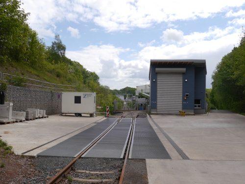 Das Foto zeigt den Gleisanschluß der Schachtanlage Asse, Mittig ist das Tor im Gleis, daneben eine Halle. Man sieht, wie die Gleise zum Schacht verlaufen. Der Förderturm ist nicht zu sehen.