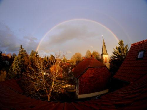 Das Foto wurde aus einem Dachfenster aufgenommen. Es zeigt einen Doppelregenbogen, der über der Dorfkirche steht. Der obere Regenbogen ist sehr schwach. Durch das Fischaugen-Objektiv wurde das BIld verzerrt.