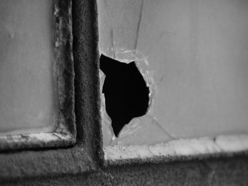 Das s/w-Foto zeigt einen Teil eines Fensters, aus der Scheibe ist ein Stück herausgebrochen, so das ein Loch entstanden ist.