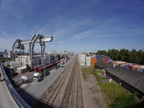 Das Foto zeigt Hafenanlagen in Mannheim, links und Rechts stehen Container, dazwischen die Ladestraße für die LKWs und Bahngleise. Durch das Fischaugen-Objektiv ist das Bild rund verzerrt..