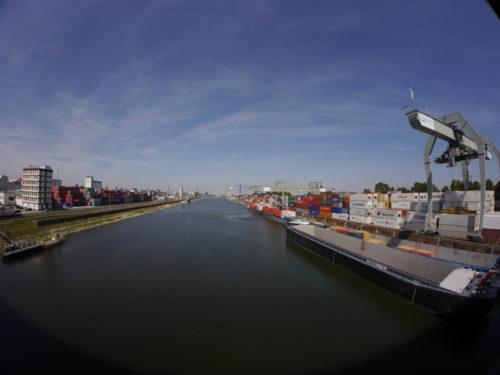 Ganz LInks sind Hafengebäude, dann das Hafenbecken, am rechten Ufer liegen zwei Schiffe, daneben der Containerkran und Containerstapel. Durch das Fischaugen-Objektiv ist das Bild rund verzerrt..