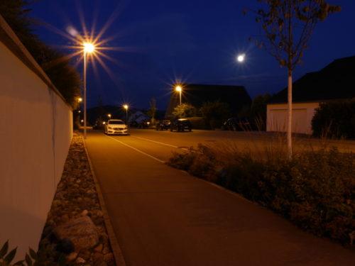 """Ds Foto zeigt eine Leere Straße in einem Wohngebiet während der """"blauen Stunde"""". DIe Straßenbeleuchtung leuchtet schon."""