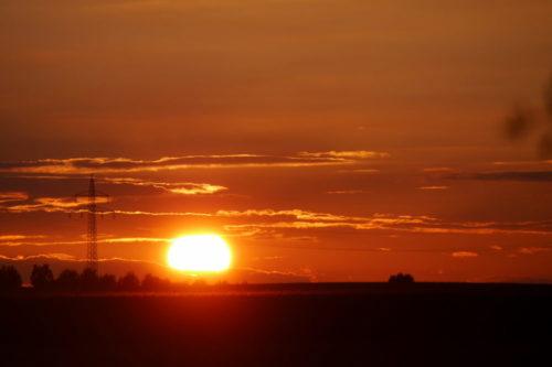 Das Foto zeigt die untergehende Sonne, die Sonnenscheibe berührt gerade die Erde...