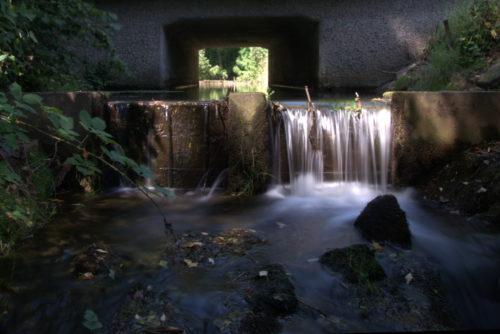Das Foto zeigt ein hölzernes Wehr in einem Bach, über das Wehr strömt das Wasser und es kommt zu einem Wasserfall. Durch die lange Belichtungszeit sieht man das Fliessen.