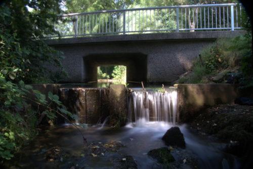 Das Foto zeigt ein hölzernes Wehr in einem Bach, über das Wehr strömt das Wasser und es kommt zu einem Wasserfall. Durch die lange Belichtungszeit sieht man das Fliessen. Außerdem sieht man die Autobrücke über dem Bach.