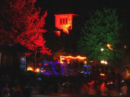 Eine Jonglier-Vorführung mit Leuchtstäben beim Lichterfest, im Hintergrund der angestrahlte alte Schlauchturm