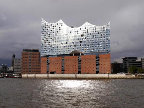 """Das Foto zeigt die Elphiharmonie von Hamburg vom Wasser her. Die Sonne spiegelt sich zum einen in den """"Fenstern"""" der Glasfassade, zum anderen von da auf das Wasser."""