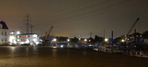 Eine nächtliche Hafenszene, das Hafenbecken ist nicht zusehen, aber der Platz und man erkennt Schiffe und Kräne