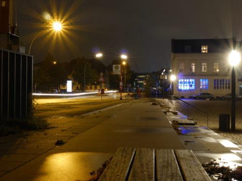 Eine Straße in der Nähe vom Hafen. An der Straße ist eine Bushaltestelle und eine Treppe führt auf einen tiefer gelegenen Platz.