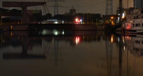 Ein nächtliches Hafenbecken mit bunten Lichtern und einer Klappbrücke