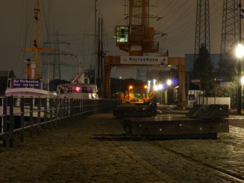 """Das Denkmal """"Kulturkan"""", ein alter, gelber Hafenkran, bei Nacht. Unter dem Kran sind ein paar """"Liegen"""" auf den alten Bahngleisen, rechts im Hafenbecken liegen alte Schiffe, das erste ist zu verkaufen."""