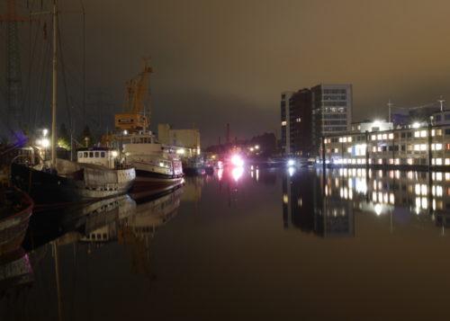 Ein nächtliches Hafenbecken, auf der linken Seite sind Schiffe und ein gelber Kran, auf der rechten Seite ein Unterkunfts-Schiff mit erleuchteten Zimmern.