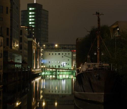 Das Foto zeigt einen nächtlichen Kanal, auf der rechten Seite liegt ein Schiff, am Ende des Kanals ist ein erleuchteter Kai und ein weißes Gebäude.