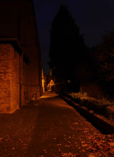 Die Nachtaufnahme zeigt einen Weg an einer Kirche, die Kirche ist auf der Linken Seite, rechts ist ein Park. Am Ende des geraden Weges sieht man ein Fachwerkhaus.