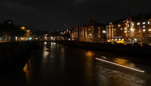 Das Foto zeigt eine NAchtaufnahme der Speicherstadt, in der Bildmitte ist ein Kanal, auf dem eine Barkasse fährt. Rechts sind Gebäude (auch der Hamburg Dungeon) und weiter hinten eine Brücke