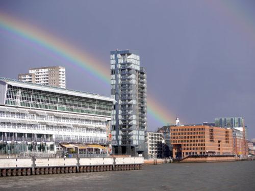 Das Foto zeigt einen Regenbogen im Hamburger Hafen, das Bild ist von der Elbe her aufgenommen und ein Hochhaus schneidet durch den Regenbogen.