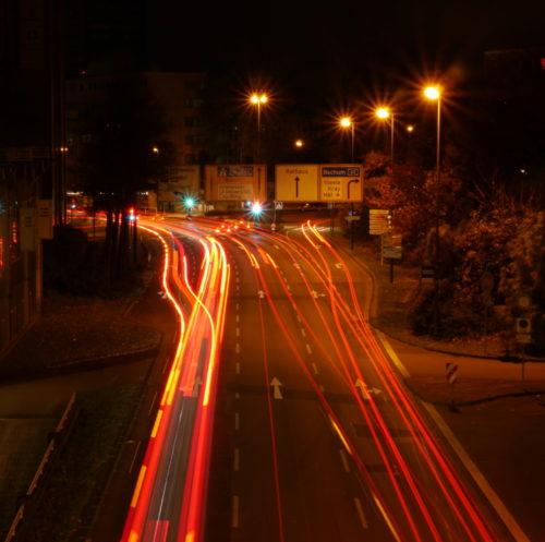 Das Foto zeigt eine Nachtaufnahme von einer Straße in Essen, die Autos fahren alle von dem Fotografen weg, daher sieht man nur die Rücklichter als rote Streifen (und teilweise die Blinker als gelbe Streifen). E ist eine Mehrspurige Straße, bei der man in verschiedene Richtungen abbiegen kann.