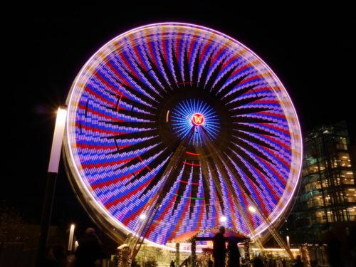 Ein Farbfoto von einem Riesenrad. Durch die Drehbewegung sind die einzelnen Lichter als Lichtspuren dargestellt. Durch die Lichtkunst erscheint eine Art bunte Sonne auf dem Reisenrad.