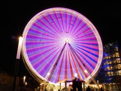 Ein Farbfoto von einem Riesenrad. Durch die Drehbewegung sind die einzelnen Lichter als Lichtspuren dargestellt.