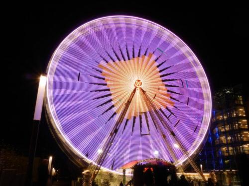 Ein Farbfoto von einem Riesenrad. Durch die Drehbewegung sind die einzelnen Lichter als Lichtspuren dargestellt. Von der Lichtkunst wird ein Rechteck auf dem Riesenrad eingeblendet.