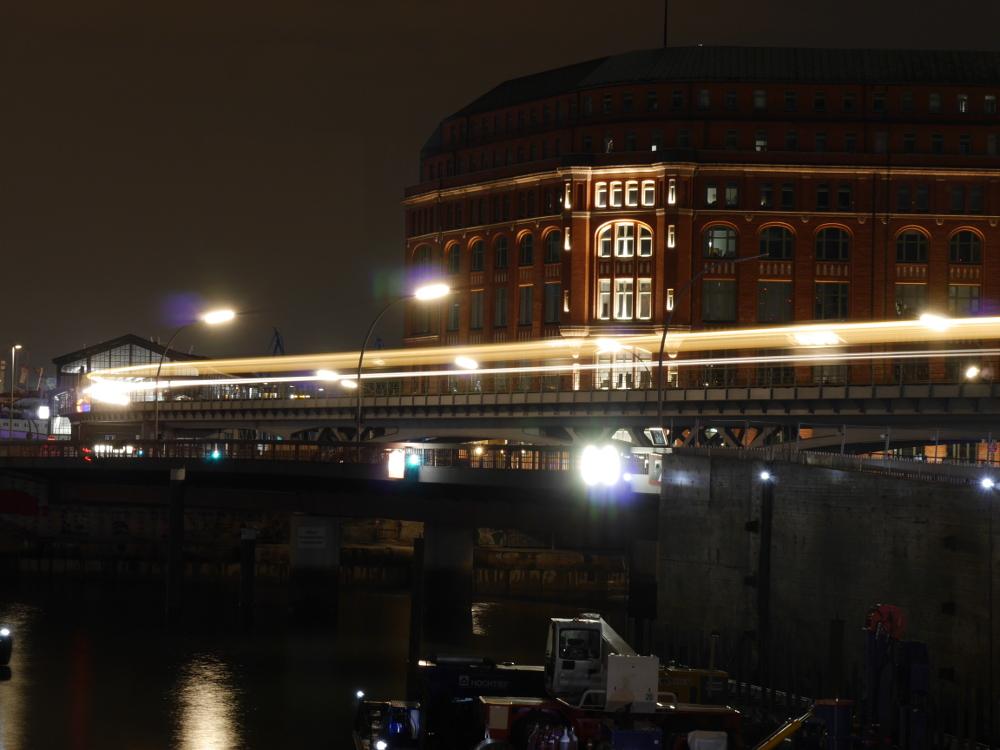 Das Foto zeigt eine Nachtaufnahme eines Hochbahngleises an der Elbe in Hamburg, vom Zug, der auf dem Gleis fährt sieht man nur die weißen Streifen der LIchter