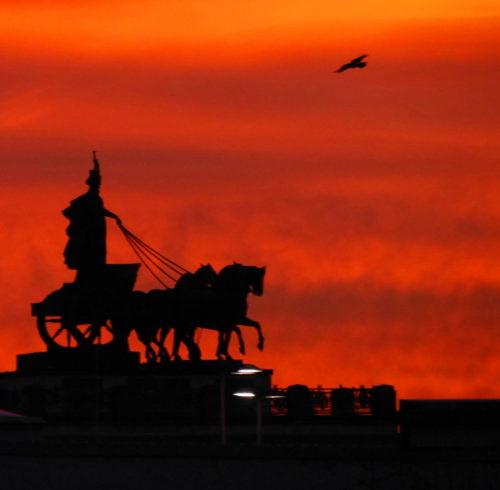 Das Foto zeigt die Quadriga auf dem Braunschweiger Schloß während eines Sonnenuntergangs, der Himmel ist durch den Untergang rot gefärbt